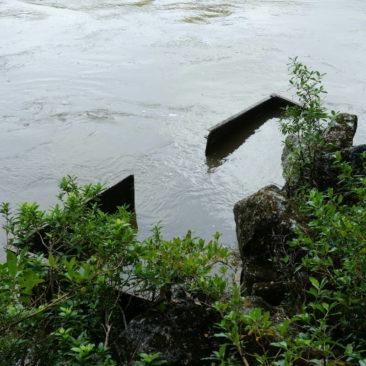 Das fast vollständig im Hochwasser führenden Fluss versunkene Eisenbahnwrack nahe Westport