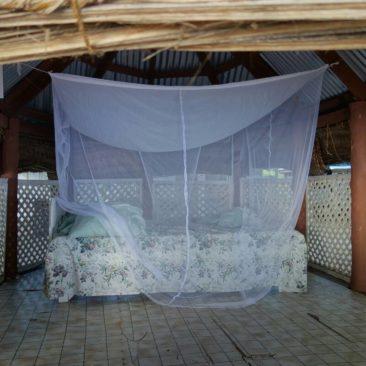 Bett mit Moskitonetz - im Inneren einer Fale