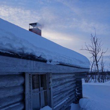 Ein rauchender Schornstein signalisiert eine warme Hütte