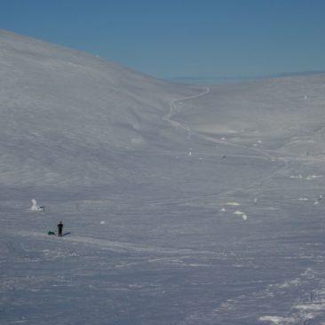 Finnische Weite mit Winterwanderer und Hütte